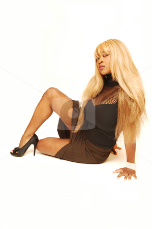Young Jamaican girl. stock photo, An busty young Jamaican girl in a black top and brown skirt with long blond   hair sitting on the floor in a studio for white background. by Horst Petzold