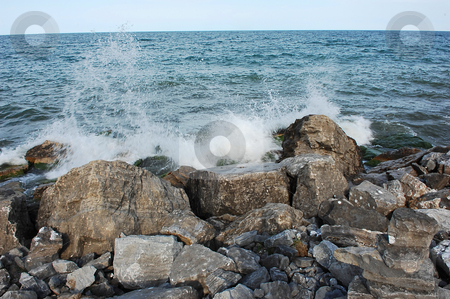 Lake shore with rocks. stock photo, Lake Ontario shore with big rocks and waves splashing on the rocks. by Horst Petzold
