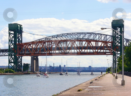 Lift bridge   stock photo, An lifted up lift bridge over the canal to the harbor of Hamilton with sparkling water waves and several small sailboats. by Horst Petzold