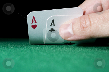 Aces stock photo, Hand holding a pair of aces on green gaming table - focus on cards and hand by iodrakon