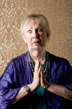 Funny New Age Lady stock photo, Funny senior new age lady in purple praying by Scott Griessel
