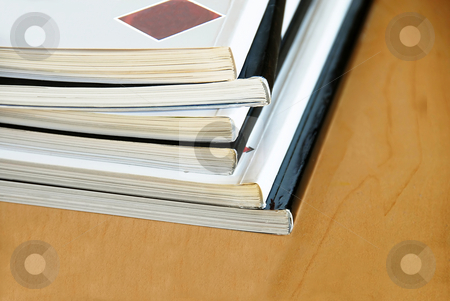 Magazines pile stock photo, Black and white magazines  pile closeup on wooden desk by Julija Sapic
