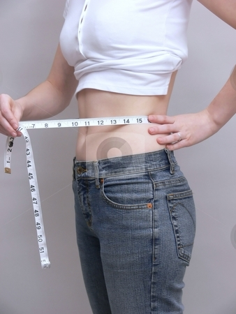Young girl    stock photo, A young girl is measuring her waist for weight lose. by Horst Petzold