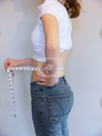 Young girl     stock photo, Young girl measuring her waist after a diet for her stomach. by Horst Petzold