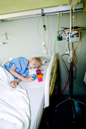 Sick boy in hospital bed looking dizzy at his toy stock photo, Portrait of a sick young boy after an operation in his hospital bed. by Frenk and Danielle Kaufmann