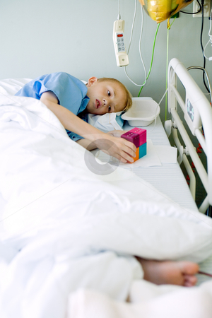 Sick boy in hospital bed with his toy stock photo, Portrait of a sick young boy after an operation in his hospital bed. by Frenk and Danielle Kaufmann