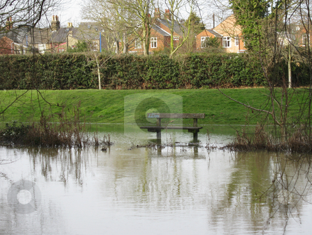 Flooded Riverside Bench stock photo, Heavy overnight rain after heavy snow meant the River Colne flooded its' banks in February 2009. The line of vegetation is usually at the top of the riverbank! by Helen Shorey