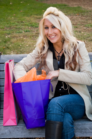Shopper Girl stock photo, A young woman reaches into one of her many shopping bags. by Todd Arena