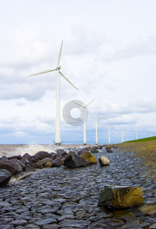 Wind turbines in a row stock photo, The wind turbines along a dyke in the netherlands by Corepics VOF
