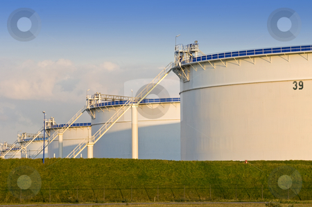 Storage tanks stock photo, Oil storage tanks in the evening light by Corepics VOF