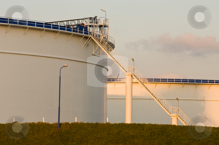 Oil tanks in the evening light stock photo, Oil tanks in the warm glow of the evening light by Corepics VOF