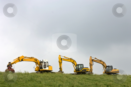 Yellow Goods stock photo, Three diggers, parked on a dyke in Zeeland, the Netherlands by Corepics VOF