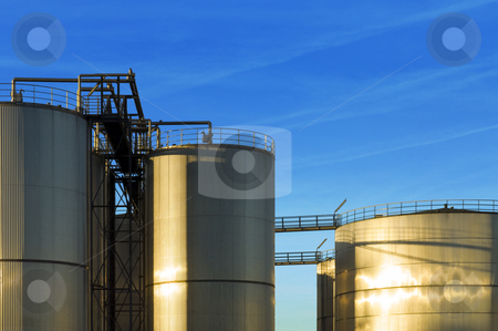 Stainless steel industrial Silos stock photo, An industrial plant with huge stainless steel silos, reflecting in the evening sun by Corepics VOF