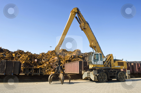 Scrap Heap Crane stock photo, A crane with a huge claw in front of a steel scrap heap by Corepics VOF