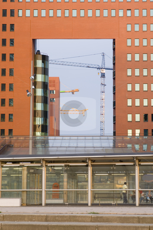 Inner City see-through stock photo, A glimpse underneath a modern office building at a construction site, with cranes lit by the last rays of the sun on a summer evening by Corepics VOF