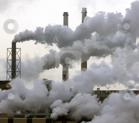 Heavy Industry stock photo, A heavy industry production plant with steam and fumes from various exhausts by Corepics VOF
