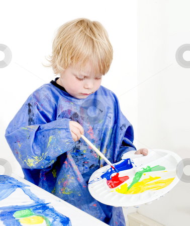 Mixing poster paint stock photo, A young boy with a palette in his hand mixing poster paint with a brush by Corepics VOF
