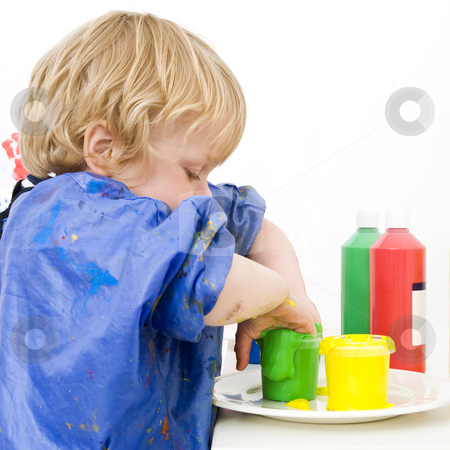 Green finger paint  stock photo, A boy putting both his hands in a pot of green finger paint by Corepics VOF