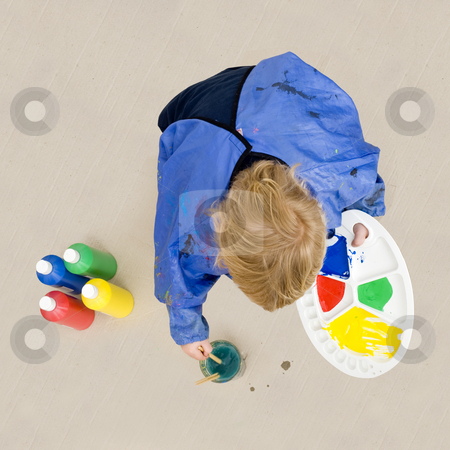 Rinsing a paint brush stock photo, A small boy, crouching down to rinse a brush which he used with poster paint for a painting on a huge cardboard surface by Corepics VOF