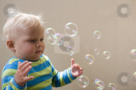 Bubble play stock photo, A young child intrigued by the soap bubbles floating around him by Corepics VOF