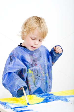 Avid painter stock photo, A young boy absorbed with painting with poster paint by Corepics VOF
