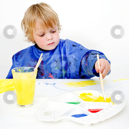 Reaching for the palette stock photo, A young painter reaching for the yellow poster paint on his palette by Corepics VOF
