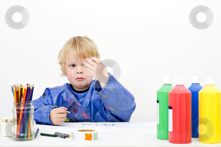 Broken crayon stock photo, A young boy looking sadly at the tip of a broken crayon in his hand by Corepics VOF