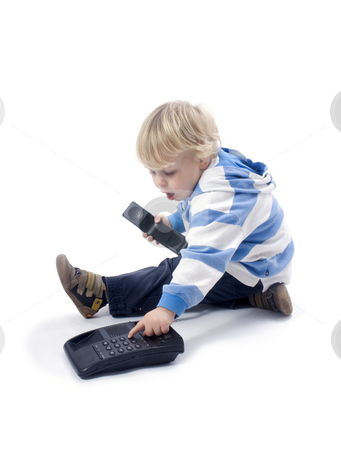 Dialling boy stock photo, A small 3 years old boy dialling a phone and pressing buttons by Corepics VOF