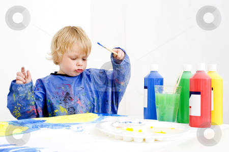 Painter boy stock photo, A young boy making a painting with poster paint by Corepics VOF