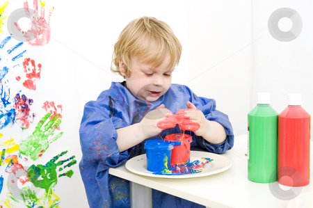 Finger painting stock photo, Boy with an apron playing with various colors finger paint by Corepics VOF