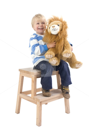 Boy with toy lion on a stool stock photo, A young, 3 years old boy sitting on a stool, holding a toy lion and smiling by Corepics VOF