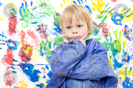 Fullfilled artist stock photo, A young boy, looking snug and contented after making a colorful fingerpaint painting by Corepics VOF