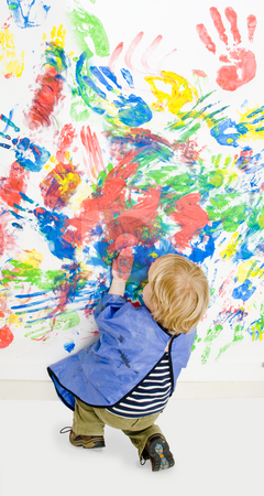 Finger painting stock photo, Young boy busy finger painting, kneeling down, to finish hsi work by Corepics VOF