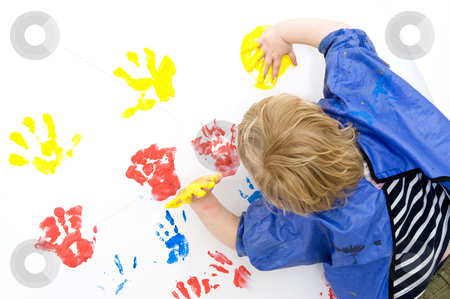 Finger painting stock photo, A boy wearing an apron busy finger painting, with his hands covered in yellow paint by Corepics VOF