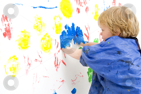 Finger painting stock photo, A young boy pressing his hands, covered with blue paint, against a wall, making prints with finger paint by Corepics VOF
