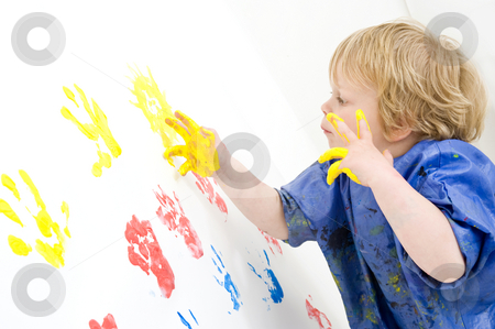 Young Artist stock photo, A young boy, attentively working on a finger painted painting on a wall by Corepics VOF