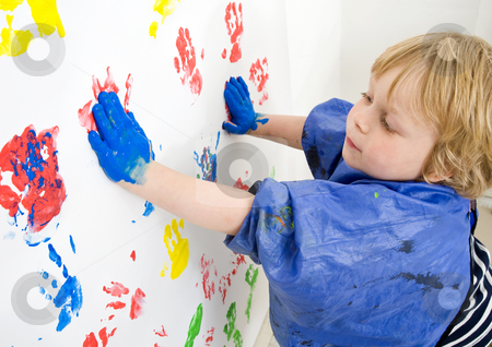 Painting boy stock photo, A boy finger painting with blue acrylic paint on a wall by Corepics VOF