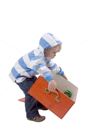 Boy lifting box stock photo, A three years old boy lifting a wooden toybox by Corepics VOF