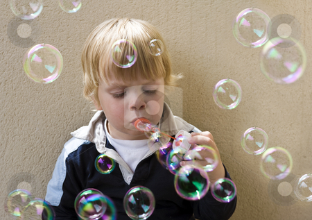 Blowing bubbles stock photo, A young blonde boy blowing bubbles by Corepics VOF