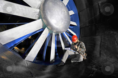 Windtunnel mainenance worker stock photo, An engineer working through a checklist on a clipboard in front of the huge blades of a windtunnel by Corepics VOF