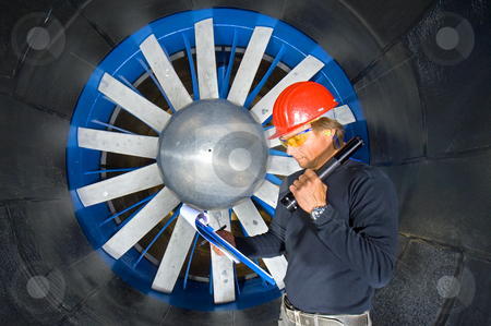 Reading notes stock photo, An engineer, wearing a hardtop, protective goggles and ear protection, reading his notes in front of the huge rotor of an industrial windtunnel by Corepics VOF