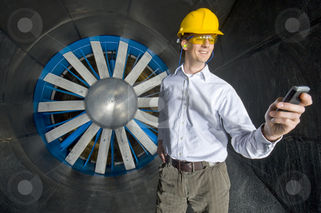 A smiling engineer, looking at his phone stock photo, A smiling engineer, looking at his phone inside the realms of an industrial windtunnel by Corepics VOF