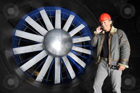 Engineer in a wind tunnel stock photo, An engineer, calling, in front of the huge rotor blades of a windtunnel in a testing facility by Corepics VOF