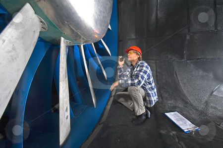 Inspecting a windtunnel stock photo, An engineer, wearing a checkered shirt, inspecting the rotors of a huge industrial windtunnel by Corepics VOF