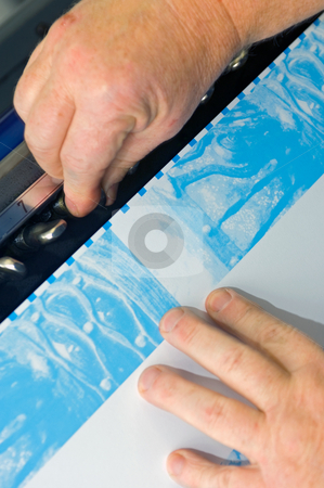 Calibrating stock photo, Two hands calibrating the tone of the Cyan pass during full color offset printing by Corepics VOF