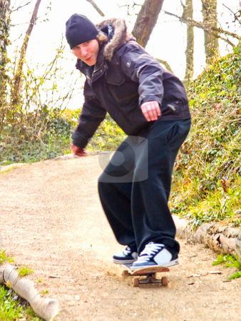 Excited young guy skateboarding down a hill stock photo, Excited young guy skateboarding down a path by Phillip Dyhr Hobbs
