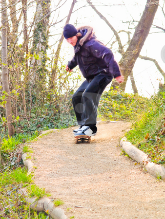 Worried young guy skateboarding down a path stock photo, Worried young guy skateboarding down a  path by Phillip Dyhr Hobbs