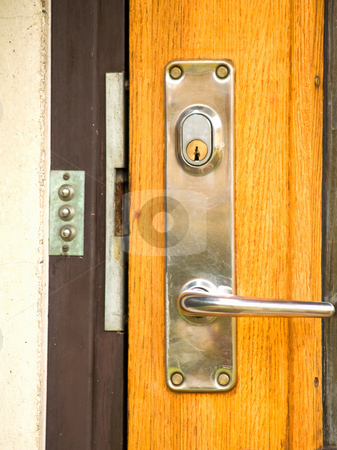 A modern day lock on a front door stock photo, A modern day lock on a  front door by Phillip Dyhr Hobbs