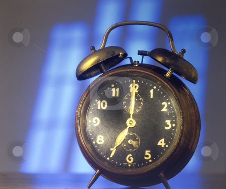 Old alarm clock stock photo, Old alarm clock in the shadow of a window by Jonathan Hull