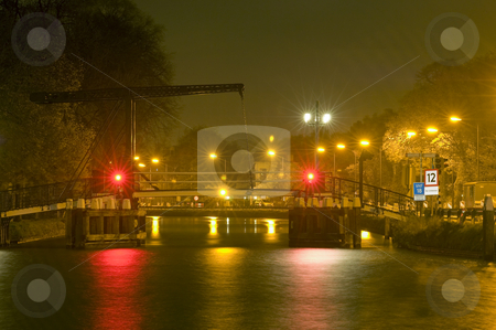 Drawbridge at night stock photo, A drawbridge at night during a shower of rain with gusts of wind by Corepics VOF